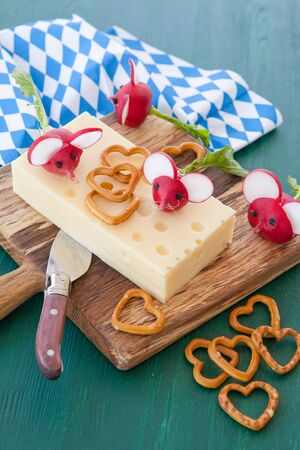 hard cheese: Block with hard cheese with radishes on wooden cutting board