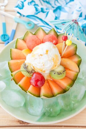 fruity salad: Fresh fruit salad with ice cream  in a cantaloupe melon cup Stock Photo