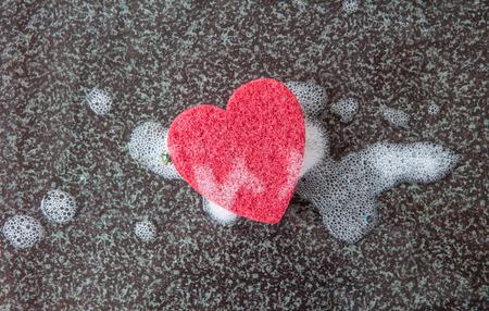 neatness: Red kitchen sponge in a heart shape on dark background