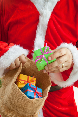 burlap sack: Santa Claus handing out colorful presents from a burlap sack Stock Photo