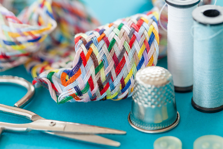 kit de costura: Colorful sewing kit with yarn and scissors on blue Foto de archivo