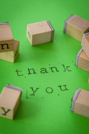 Thank you note written with rubber stamps on green