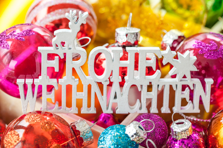 translates: Christmas baubles in various bright colors as a background, Frohe Weihnachten translates to Merry Christmas Stock Photo