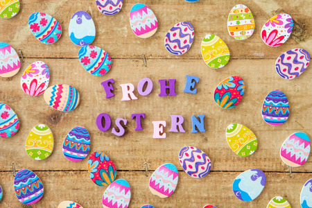 translates: Multicolored eggs on a rustic wooden background for easter, Frohe Ostern translates to Happy Easter
