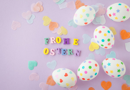 translates: Easter eggs with colorful sticker hearts and dots, Frohe OStern translates to Happy Easter