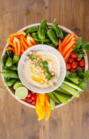 Homemade hummus with olive oil and fresh vegetables