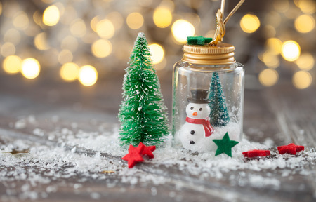 Festive christmas decorations on snow in front of bokeh lights