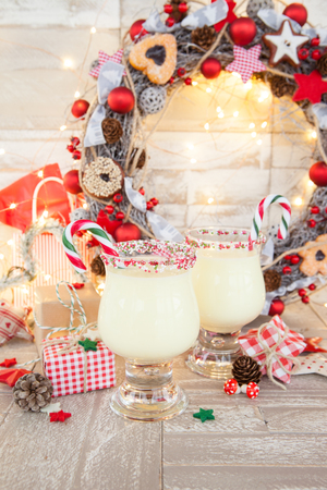 Egg nog with candy cane and sugar sprinkles