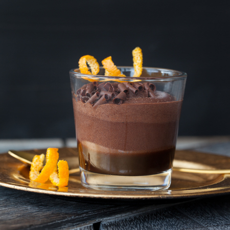 Layered chocolate dessert with orange in a glass