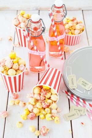 Colorful popcorn in striped cups and lemonade in vintage bottles Stockfoto