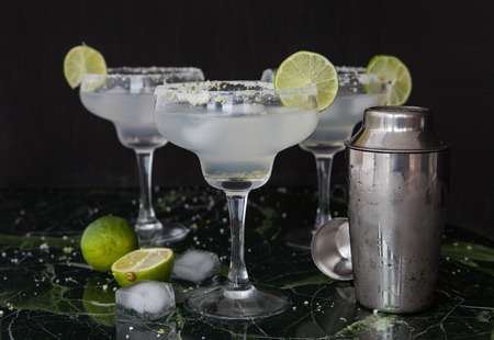 Ice cold Margarita Cocktails in stem glasses with salted rim
