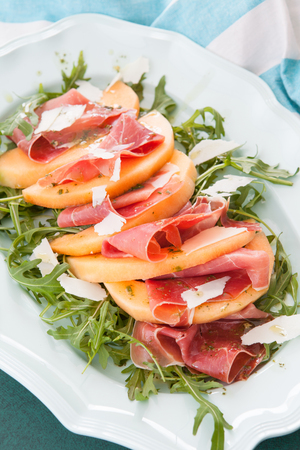 Colorful summer salad with fresh cantaloupe and Serrano ham