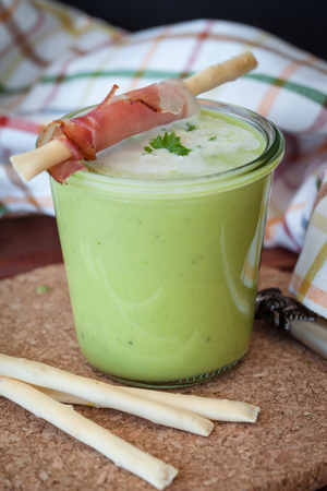 Homemade creamy pea soup and bread sticks with smoked ham
