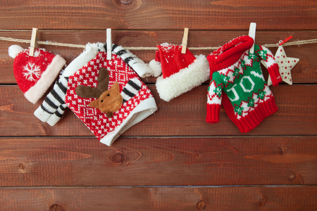 Little knitted christmas pullovers on a wooden background Stock Photo