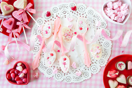Pink spoons with white chocolate and sugar sprinkles