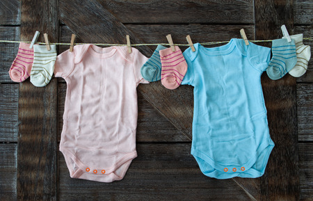 Baby clothing in pink and blue on rustic wooden background