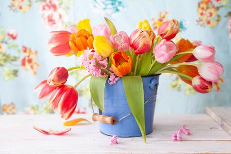 Coloridas flores de primavera en un pequeño balde vintage