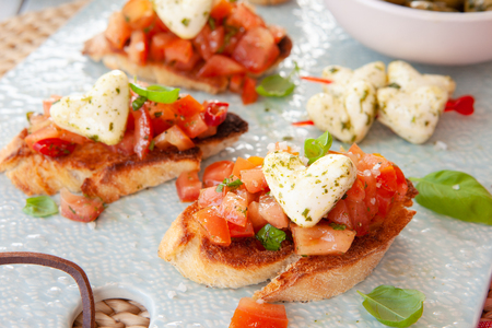 Toasted baguette bread with tomatoes and heart shaped mozzarella cheese