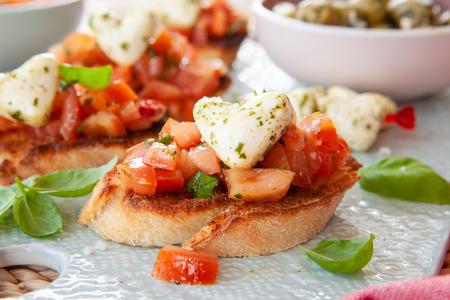 Geröstetes Baguettebrot mit Tomaten und Mozzarella in Herzform Standard-Bild