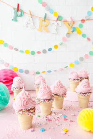 Pink soft serve ice cream with colorful sprinkles in little waffle cups