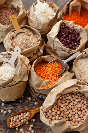 Variety of dried legumes and grains in little paper bags