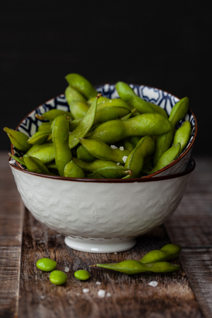 Bowls of fresh green soy beans with salt Stockfoto
