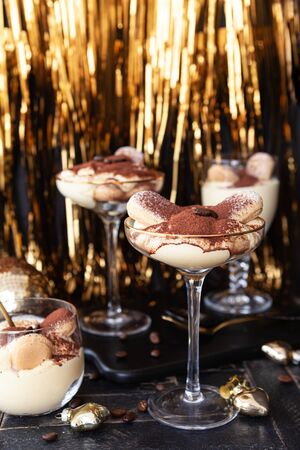 Festive tiramisu dessert in glasses with golden decorations for the holidays 写真素材