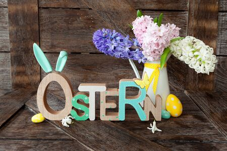 Cheerful easter decorations and a bunch of fresh spring flowers, Ostern translates to Easter