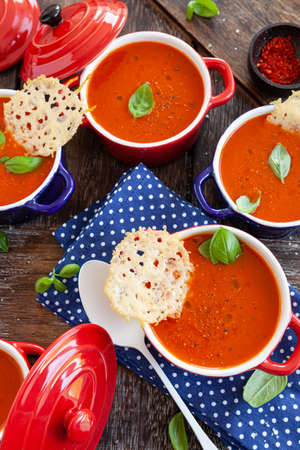 Homemade tomato soup in little pots with parmesan crackers