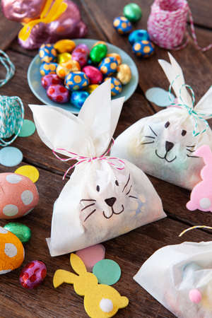 Little gift bags with colorful chocolate eggs for Easter