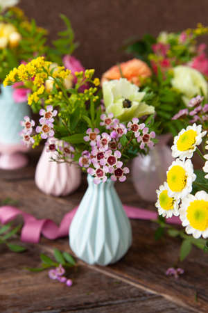 Fresh spring flowers in little vases, rustic wooden background