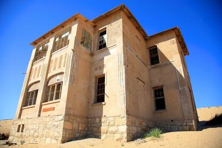 kolmanskop: Abandoned house a blue sky and the desert of sand all around in Kolmanskop.