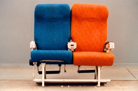 love seat: Orange and blue isolated aircraft seats Stock Photo