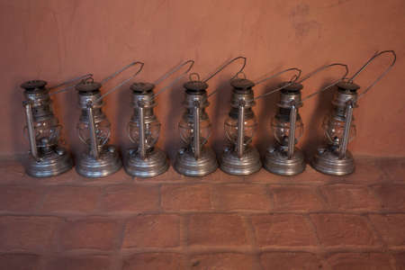 Seven Metal Oil Lamps shot on wall Background