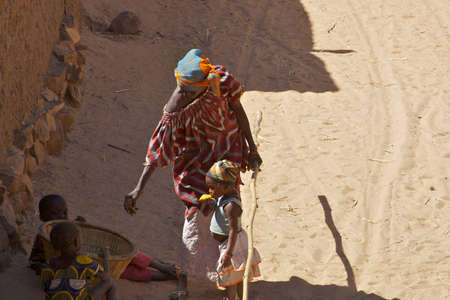 Dogon woman on a sandy track with her chldren