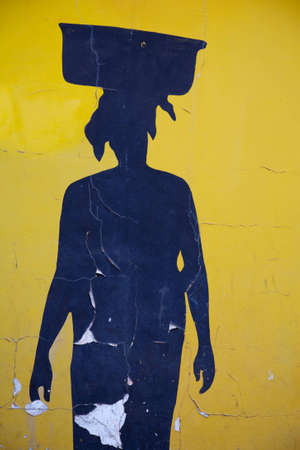 bamako: Blue shape of an African woman carrying something on her head on yellow background in Bamako
