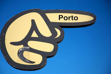 Board with hand pointing the direction to the port of Porto with a fresh blue sky