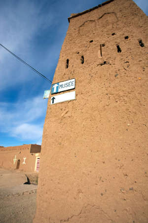 Old Moroccan house with a signboard to the musem with blue sky