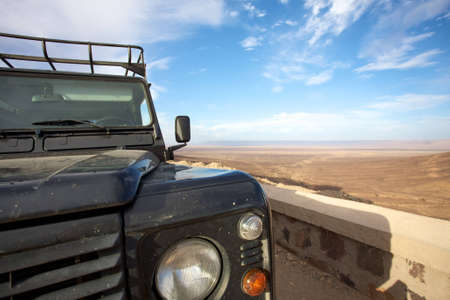 car going towards a pass in Morocco with view of the desert behind and a blue sky with clouds