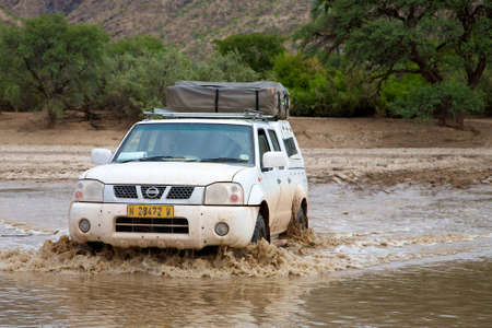 Crossing of a river by 4x4 in Namibia - Kaokoland Stock Photo - 12662483