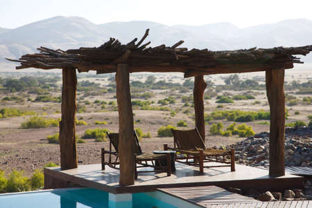 Relax chairs under a wood roof and a swimming pool facing the desert of Namibia