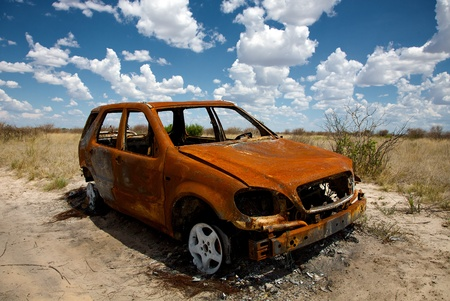 kalahari desert: A wide angle view of a rusty old abandoned car under puffy blue skies in the Game Reserve of Central Kalahari in Botswana