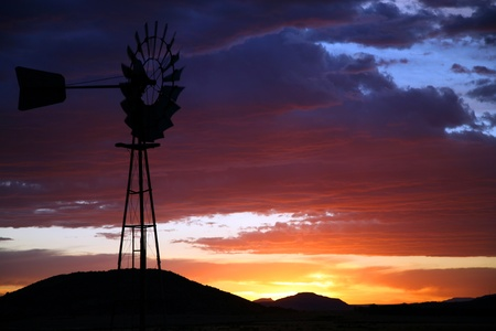 Old Farm Windmill for Pumping Water with Spinning Blades at Sunset in South Africa photo