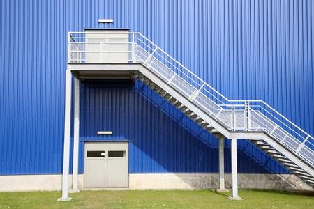 Blue Depot factory with green grass Standard-Bild