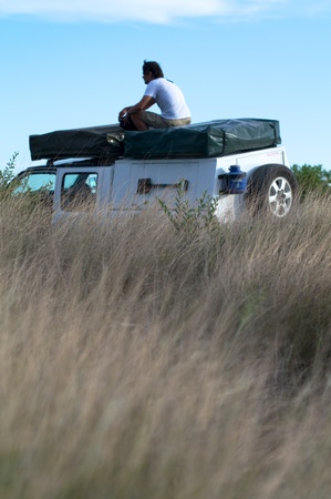 Sitting on the roof of the car in central kalahari desert photo