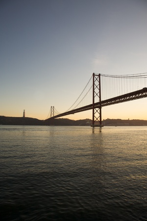made in portugal: View of the April 25th Bridge in Lisbon, Portugal. This bridge is connecting Lisbon to the municipality of Almada on the south bank of the Tagus River. Statue of Jesus in the background.