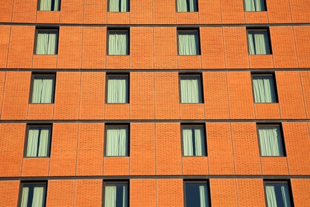 Facade of a brick office building with successive rows and floors of tinted glass windows. photo