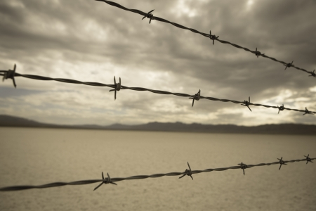 Barbed wire against cloudy sky over desert landscape in Nevada. Selective focus on barbed wire. photo