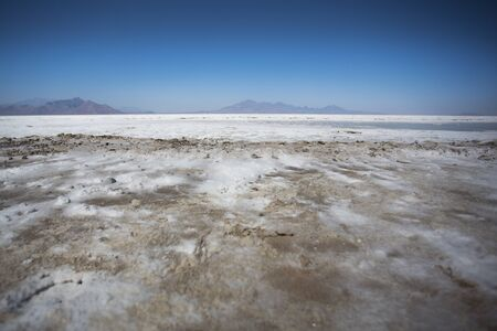 World famous Bonneville Salt Flats outside Salt Lake City Utah with mountains and blue skies. Detail of the salt on the ground photo
