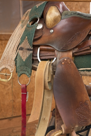 tooled: Saddle with lariat & spurs on old weathered barn wood